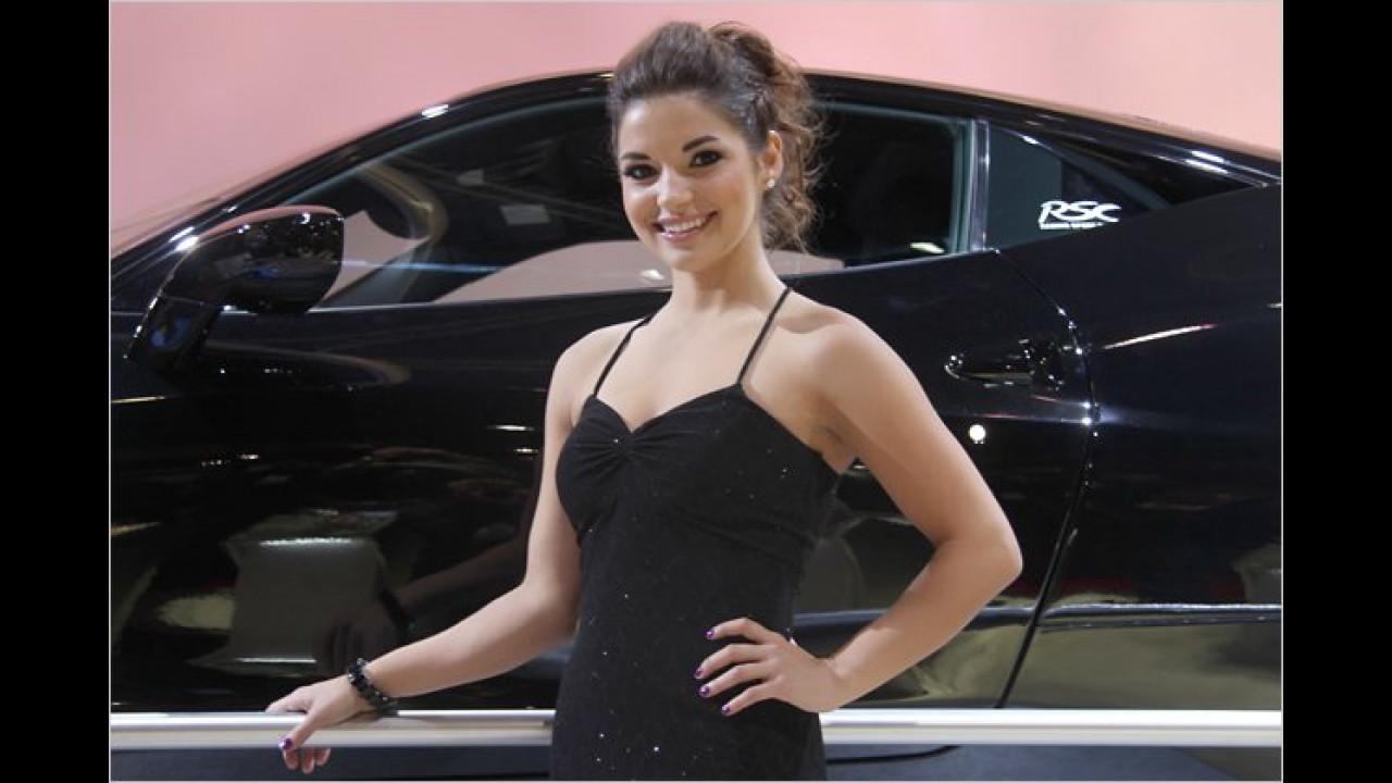 Entweder steht das Auto im Hintergrund auf einem Podest, oder die Dame ist sehr niedrig