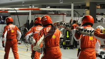 Ferrari pit crew carrying fuel hose